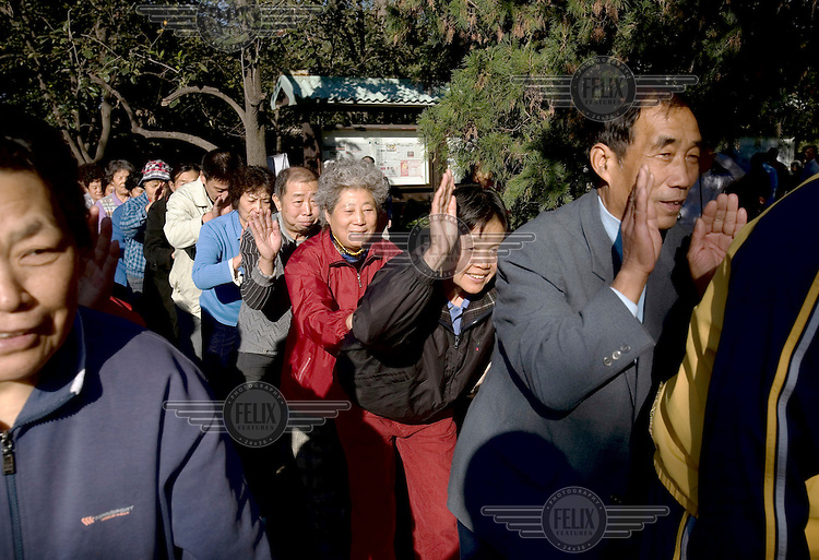 People line up in a row to massage one another's backs in a park in Beijing..