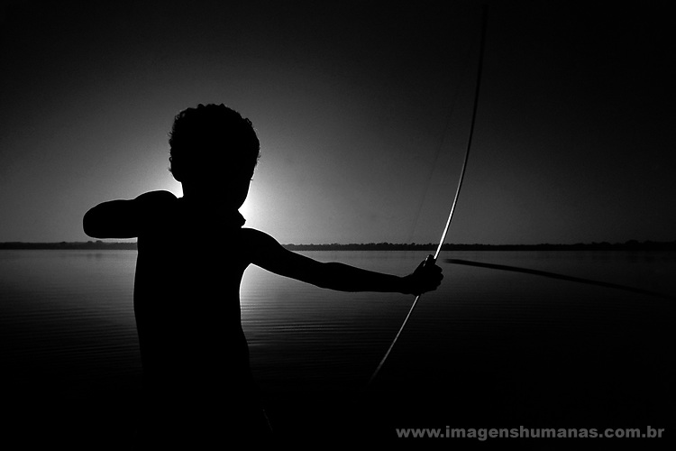 Indian boy using bow and arrow, Araguaia river, Pará State, Amazon rain forest, Brazil.