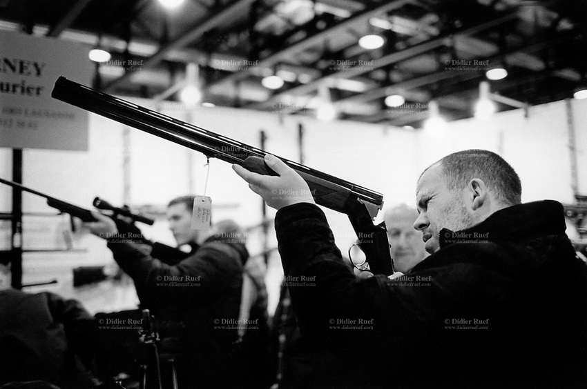 Switzerland. Canton Vaud. Lausanne. 23rd Bourse Internationale aux armes. The international gun show is a fair for hunting, sporting and melee weapons, but also for small arms, handguns and machine guns. It takes place once a year at the convention and exhibition center Beaulieu in Lausanne. A meeting point for exhibitors, customers and collectors, in order to buy or sell modern and old weapons. A man is checking a hunting rifle. 9.12.2016 © 2016 Didier Ruef