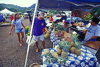 Farmers community market scene in Hanalei Town, man selecting pineapples, Hanalei, Kauai