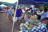 Farmers community market scene in Hanalei Town, man selecting pineapples, Hanalei, Kauai
