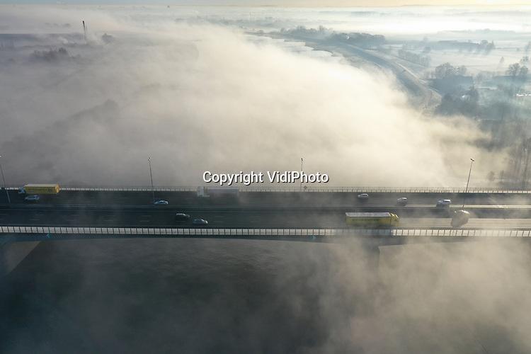 Foto: VidiPhoto<br /> <br /> HETEREN &ndash; Het was even schrikken vrijdagmorgen voor automobilisten op de A50 ter hoogte van Renkum en Heteren. Een dikke en hardnekkige nevel in het Betuwse rivierengebied en boven de Rijn zorgde tijdelijk voor minder zicht tijdens de spits. Omdat het vrijdagsmorgens minder druk is op de weg, zorgde dat niet voor grote hinder. Wel voor een mooi plaatje vanuit de lucht, met zicht op het viaduct over de Rijn bij Heteren. Nu het &rsquo;s nachts gaat vriezen en het ook overdag een stuk kouder wordt, is de kans op mist en nevel in de ochtend de komende week vrij groot.