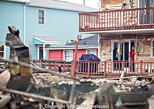 BREEZY POINT-NEW YORK-OCTOBER 31: A young woman looks out at the burned out ruins in this community devastated by Hurricane Sandy October 31, 2012. Over a 100 homes were lost to fire and many others were damaged by wind and flooding.