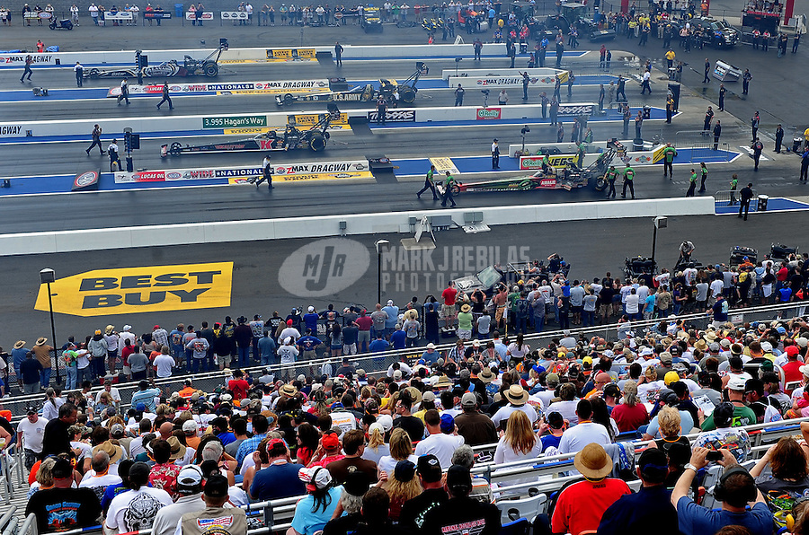 Apr. 15, 2012; Concord, NC, USA: NHRA top fuel dragster drivers back up in front of the fans in the grandstands during eliminations for the Four Wide Nationals at zMax Dragway. Mandatory Credit: Mark J. Rebilas-