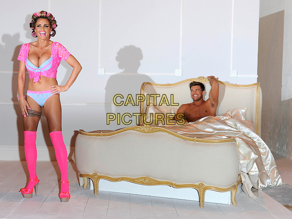 Katie Price (Jordan) & Leandro Penna.The launch photocall for Katie Price's new summer lingerie range for Store 21, The Worx, London, England..May 29th, 2012.full length pink lace top knotted bra cleavage belly stomach midriff knickers underwear tights stockings tattoo garter beige platform sandals shoes rollers curlers in hair side bed chest topless couple hand on hip arm in air smiling.CAP/DH.©David Hitchens/Capital Pictures.