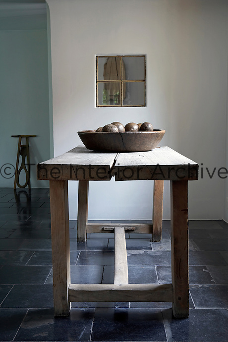 An antique walnut bowl containing an ancient set of boxwood boules sits on an old oak farmhouse table in the entrance hall