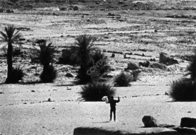 Gilles Caron waves a white piece of material to stop gouvernmental fires during the ambush, Aouzou oasis, Chad, February 1970; photograph by Raymond Depardon
