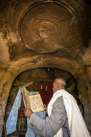 The priest of  the Mikael Melehayzenghi rock hewn church reads his bible.