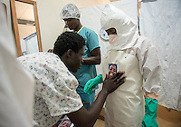 "Health care worker Deddeh Y. Miller finishes donning her PPE, complete with photo stuck to her chest, as she prepares to enter the ""red zone"" to care for patients at the ELWA II ETU (Ebola treatment unit) in Monrovia, Liberia on Sunday, March 1, 2015. Their photos were created as part of Occidental College professor Mary Beth Heffernan's PPE Portrait Project.<br /> (Photo by Marc Campos, Occidental College Photographer) Mary Beth Heffernan, professor of art and art history at Occidental College, works in Monrovia the capital of Liberia, Africa in 2015. Professor Heffernan was there to work on her PPE (personal protective equipment) Portrait Project, which helps health care workers and patients fighting the Ebola virus disease in West Africa.<br />