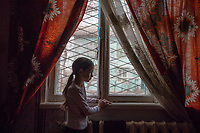 Uzbekistan - Tashkent - Ramilya, 9 stands before the window of her family's living room located in Sputnik, a satellite neighborhood entirely built in wood to accomodate a large part of the population who had lost their house in the 1966 earthquake.