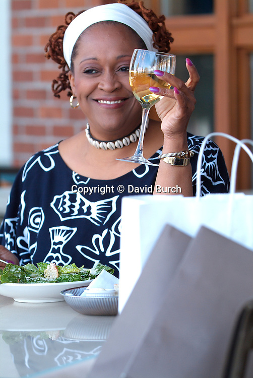 Happy African American woman eating a salad and toasting