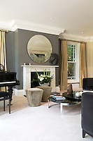 The spacious sitting room is decorated in tones of grey and gold and features a rare piano. The steel coffee table and circular mirror above the fireplace add a contemporary note to the otherwise traditionally styled room.