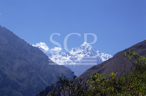 Inca Trail, Peru. View down Cusichaca valley to snowcapped peak of Mount Veronica or Waki Wilki with treetop in foreground.