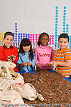 Penny Harvest at PS 100 South Ozone Park New York Common Cents vertical groups of children holding handfuls of pennies. graph of results by classoom behind them.