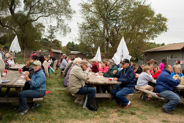 People eat snacks during the AD Makepeace Company's 10th Annual Cranberry Harvest Celebration in Wareham, Massachusetts, USA. AD Makepeace is the world's largest producer of cranberries. These cranberries, wet harvested with varied colors, are destined for processing into juice, flavoring, canned goods and other processed foods.