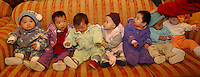 Newly adopted Chinese female babies line-up on sofas for a group photograph. The babies belong to a group of Canadian nationals going through the adoption procedure in Changsha, Hunan, China.