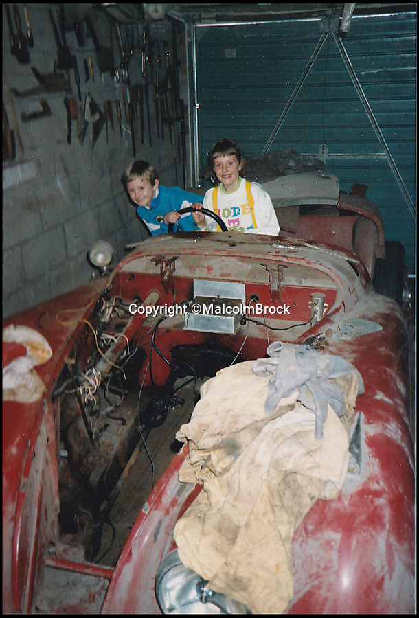 BNPS.co.uk (01202 558833)Pic: MalcolmBrock/BNPS<br /> <br /> Malcolm's daughter Tracey and her friend in the partially dismantled car, 1988. Pictured at the start of it's restoration.<br /> <br /> A pensioner who paid less than £200 for a classic Jaguar has decided to sell the car after 50 years of ownership, with experts tipping it to collect as much as £100,000.<br /> <br /> Malcolm Brock first bought his 1951 XK120 roadster as a fresh faced 19-year-old in 1969. He paid just £180 for the car and instantly fell in love with it's charm.<br /> <br /> Since then the car has been like a loyal friend to Malcolm and he holds several happy memories in it, including it carrying his daughter to her wedding over twenty years ago.<br /> <br /> Malcolm, 68, has competed in the convertible in a number hill climbing events, and also used it as his everyday run-around for several years.