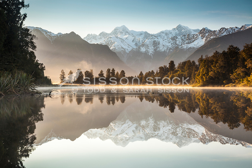 Misty Sunrise and perfect reflections of Mt Cook, Mt Tasman & Southern Alps at Lake Matheson, Westland Tai Poutini National Park NZ.