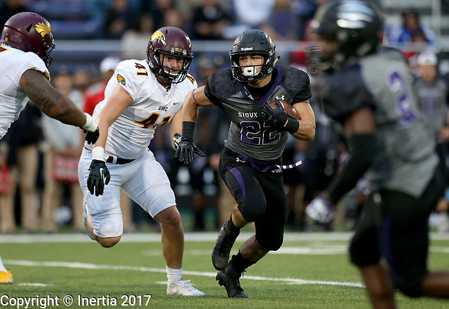 SIOUX FALLS, SD - SEPTEMBER 23: Max Mickey #22 from the University of Sioux Falls looks looks for running room past Chuck Lofquist #41 from Minnesota Crookston in the first half of their game Saturday night at Bob Young Field in Sioux Falls. (Photo by Dave Eggen/Inertia)