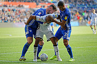 Andre Ayew of Swansea City (C) challenged by Sean Morrison (L) and Lee Peltier of Cardiff City (R) during the Sky Bet Championship match between Swansea City and Cardiff City at the Liberty Stadium, Swansea, Wales, UK. Sunday 27 October 2019