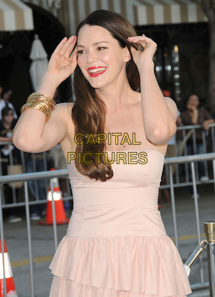 "JACINDA BARRETT .at The Warner Brother Pictures Premiere of ""Whiteout"" held at The Mann's Village Theatre in Westwood, California, USA, September 9th 2009.                                                                                      .half length strapless pale peach beige dress tiered layered ruffles gold bracelets bangles red lipstick make-up hands touching head hair smiling .CAP/DVS.©Debbie VanStory/RockinExposures/Capital Pictures"