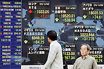 Pedestrians pass a stock market indicator board on April 30, 2015, Tokyo, Japan. The Japanese Nikkei index ended 0.83% (538.94 points ) lower at 19,520.01 on Thursday. This is the biggest drop in four moths after briefly crossing the 20,000 Yen line for the first time since April 2000. Asian markets traded lower pulled down by weak U.S. growth figures for the first three months of 2015. (Photo by Rodrigo Reyes Marin/AFLO)