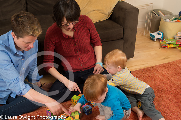 Fraternal twin boys, age 22 months, at home with parents, toddlers playing with blocks, parents pointing and talking