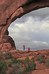 Couple visiting North Window Arch at sunset in Arches National Park, Utah, USA. .  John offers private photo tours in Arches National Park and throughout Utah and Colorado. Year-round.