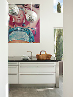 A contemporary kitchen with white and stainless steel units. The pendant lights are mirror balls by Tom Dixon.