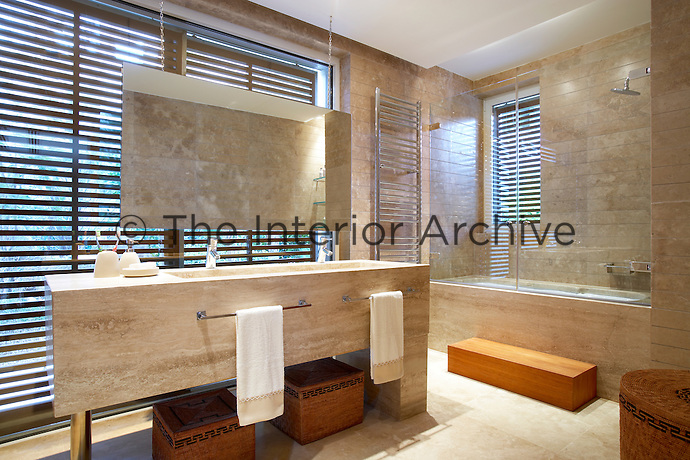 A stylish tiled bathroom with twin washbasins set in a marble unit and a shower over the bath.