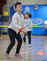 NWA Democrat-Gazette/ANDY SHUPE<br /> Dimaya Hintz, 7, of Fayetteville bounces a tennis ball on her racket Tuesday, March 27, 2018, as her sister, Phoebe Hintz, 5, chases a ball while learning how to play tennis during homeschool physical education class at the Yvonne Richardson Community Center in Fayetteville.  The center hosts physical eduction classes for homeschooled children on Tuesdays and Thursdays.
