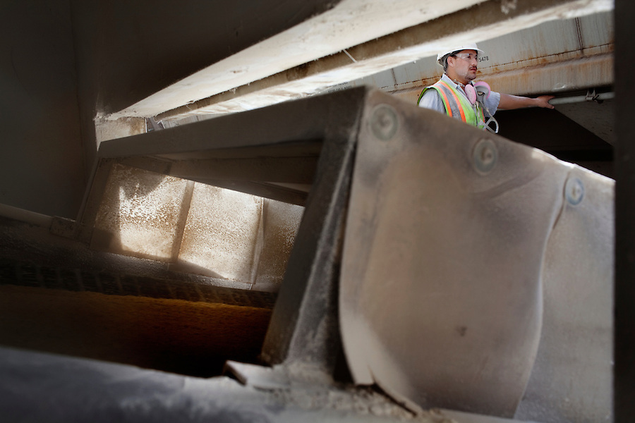 CREDIT: Daryl Peveto/LUCEO for The Wall Street Journal.Exports 2032..Los Angeles, California, March 1, 2010 -Samuel Sandovar watches as soybean meal is moved from rail cars to containers at the Los Angeles Harbor Grain Terminal.  The meal, which is a fine powder, is dropped onto a conveyer belt from the rail car. The conveyer than moves it into a machine that blows it into a container. A decline in U.S. consumption has left exports short of a good exit strategy. In 2009, imports fell 28%. This has created a bottleneck for exports, which need the shipping containers to move product overseas. ...
