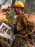 August 20, 1992 Angels Camp, California -- Old Gulch Fire—  Fulton Hotshot foreman reads the paper on Sheep Ranch Road. The Old Gulch Fire raged over some 18,000 acres, destroying 42 homes while threatening the Mother Lode communities of Murphys, Sheep Ranch, Avery and Forest Meadows.