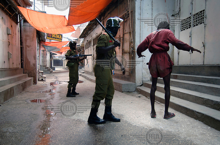 Riot police arrest a man following violent clashes in the wake of a disputed election in Zanzibar. Police and opposition supporters fought in the streets after allegations of polling irregularities.
