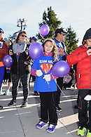 Young girl holding balloons wearing a team jersey.