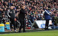 SWANSEA, WALES - FEBRUARY 07: Swansea manager Garry Monk (C) shouts instructions to his players while Sunderland manager Gus Poyet (R) stands impassive during the Premier League match between Swansea City and Sunderland AFC at Liberty Stadium on February 7, 2015 in Swansea, Wales.