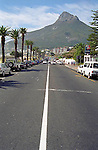The road along the beach passes through Camps Bay with a view of Lion's Head in Capetown South Africa.