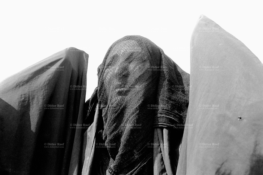 "Iraq. Basrah. Al Fao neighbourhood. A moslem woman, dressed with the abaya, looks at the procession, the celebration and the religious commemoration of the day of Ashura. Muharram is a month of remembrance that is often considered synonymous with the event of Ashura. Ashura, which literally means the ""Tenth"" in Arabic, refers to the tenth day of Muharram. It is well-known because of historical significance and mourning for the martyrdom of Hussein ibn Ali, the grandson of Muhammad. Shi'a Muslims start the mourning from the 1st night of Muharram and continue for two months and eight days. However the last days are the most important since these were the days where Hussein and his family and followers were killed in the Battle of Karbala which took place on Muharram 10, in the year 61 of the Islamic calendar (October 10, 680). Muharam's month is considerated as one of the most important feast for the Shiism branch of Islam. Shia Islam is the second largest denomination of Islam. The followers of Shia Islam are called Shi'ites or Shias. Basra ( in arabic Al Ba"