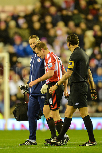 27.11.2012 Sunderland, England. Lee Cattermole, Sunderland's Captain leaves the pitch with a medic, early in the first half during the Premier League game between Sunderland and Queens Park Rangers at the Stadium of Light.