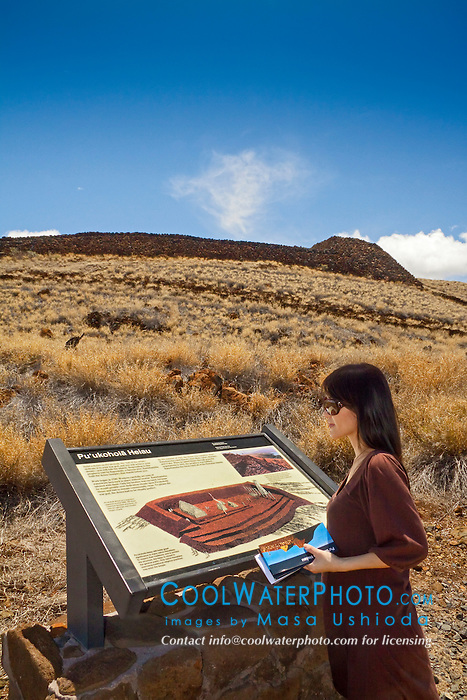 woman visitor looking at park sign at Puukohola Heiau - the temple on the whale hill, the largest and last heiau constructed in 1790-91 by Kamehameha I, Puukohola Heiau National Historic Site, Kawaihae, Kohala, Big Island, Hawaii, USA, Model Released - MR#: 000103