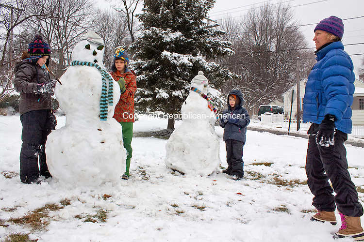 NAUGATUCK CT- JANUARY 16  2013 -011613DA05- Kris Generali, of Naugatuck takes a step back to look over the finishing touches on the pair of snowmen that she helped make along with her children, from left, Ella, 8, Trey, 10, and Reeve, 6, at their home on Wednesday..Darlene Douty Republican American