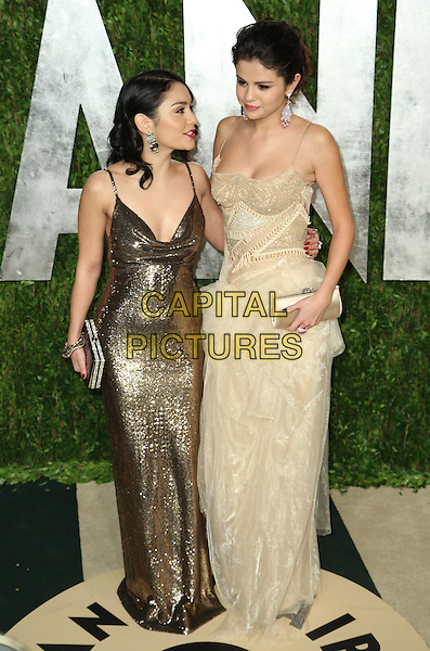 Vanessa Hudgens & Selena Gomez.2013 Vanity Fair Oscar Party following the 85th Academy Awards held at the Sunset Tower Hotel, West Hollywood, California, USA..February 24th, 2013.oscars full length white cream dress gold metallic tall short looking up profile hand on hip corset cleavage clutch bag.CAP/ADM/SLP/DOW.©Dowling/StarlitePics/AdMedia/Capital Pictures