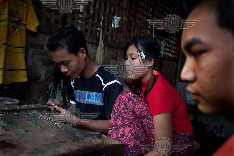 A jeweller makes a jade necklace at the Jade Market in Mandalay. Much of the Burmese junta's wealth comes from the trade in precious stones.