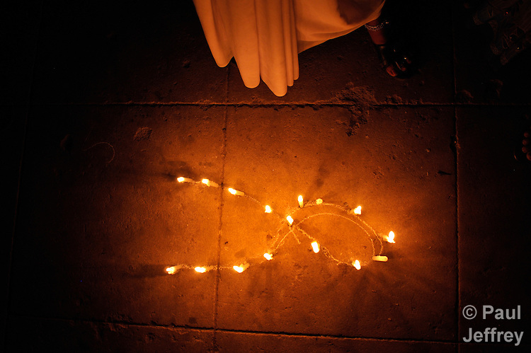 People infected by and affected by HIV and AIDS gather for a candlelight vigil in Guntur, Andhra Pradesh, India, to raise public awareness of the virus and the need to end stigma and discrimination against those living with it. Here they have places their candles on the ground in the shape of the ribbon which has become the universal symbol for AIDS awareness.