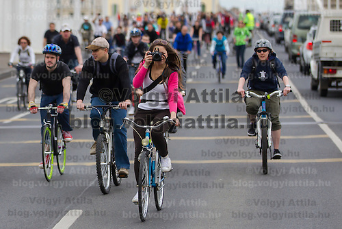 Girl takes a photo while riding participating the Critical Mass ride around the city on Earth Day that is demonstrating the importance and popularity of bicycle as a mean of everyday city transportation in Budapest, Hungary on April 22, 2012. ATTILA VOLGYI
