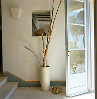 The simple entrance hall has grey-painted skirting and a travertine floor