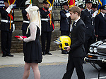 © Joel Goodman - 07973 332324 . 02/09/2013 . Bury , UK . Stephen Hunt's daughter Charlotte and son Sam carry their father's medals and a fireman's helmet to the church . The funeral of fireman Stephen Hunt at Bury Parish Church today (Tuesday 3rd September 2013) . Stephen Hunt died whilst tackling a blaze at Paul's Hair World in Manchester City Centre in July 2013 . Photo credit : Joel Goodman
