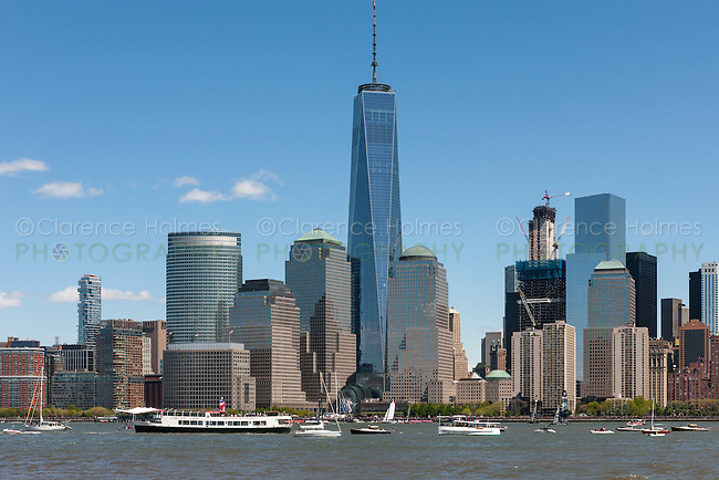 America's Cup World Series team catamarans race on the Hudson River surrounded by spectator boats in front of the Freedom Tower.