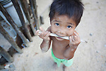 A little boy chews on a stick in El Nido, in the famous and beautiful Bacuit Archipelago in Palawan, Philippines.