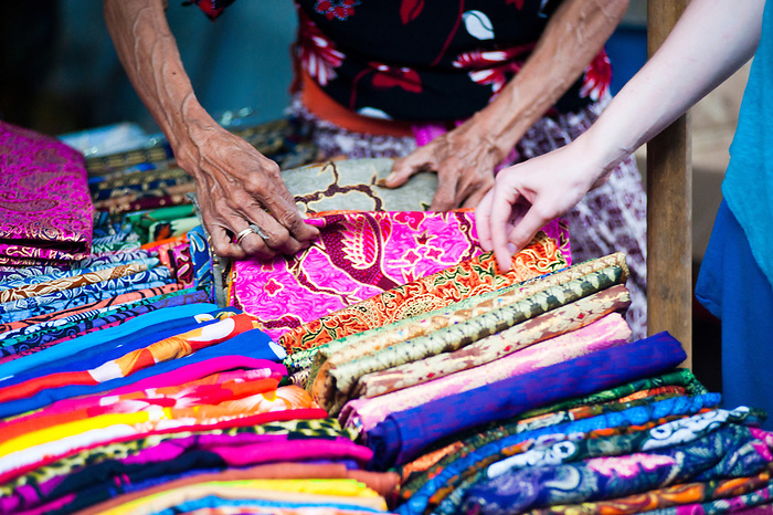 Bartering for scarves at a market stall in Ubud Market, Bali, Indonesia. Such fun....the market is full to bursting point with hand made arts and crafts, which Ubud, and Bali in general is known for. Deciding what to buy is only half the challenge, you then have to beat the haglers at their own game in an effort to pay as little above a fair price as possible!